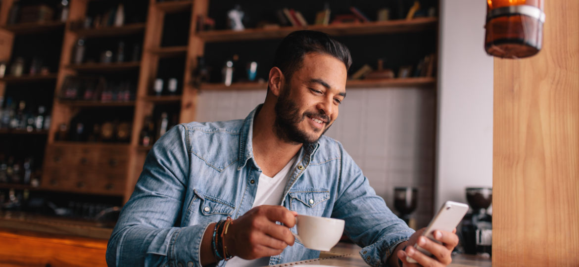 Handsome young man having coffee and using mobile phone