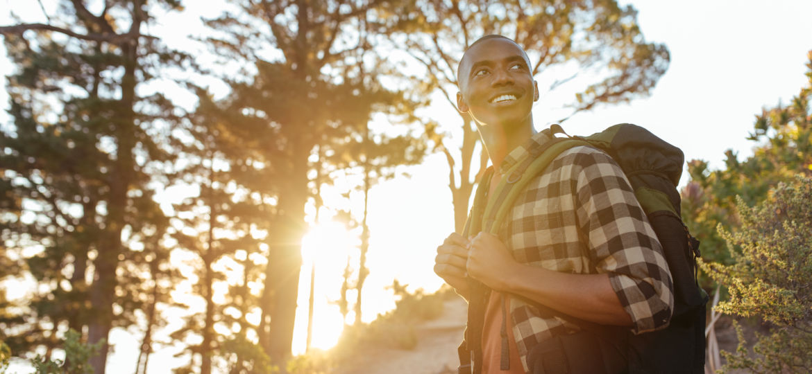 Smiling young African man hiking alone at dusk